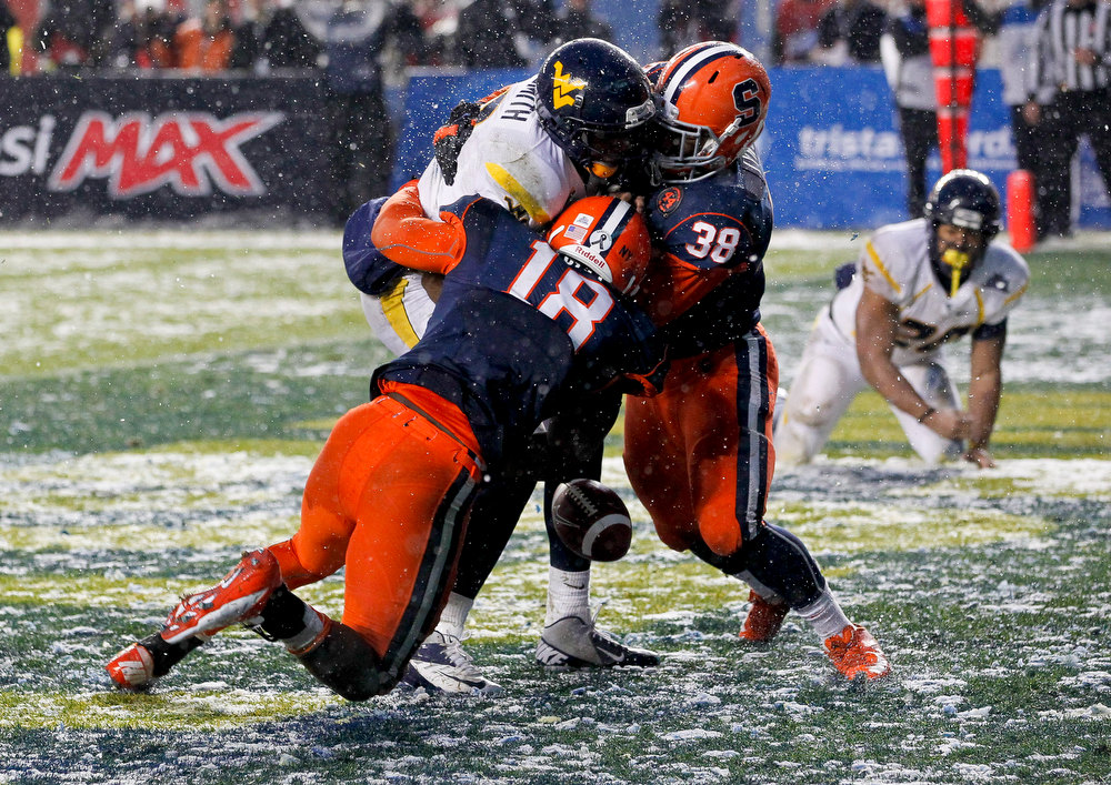 Description of . Siriki Diabate #18 of  and Cameron Lynch #38 of the Syracuse Orange sack Geno Smith #12 of the West Virginia Mountaineers in the New Era Pinstripe Bowl at Yankee Stadium on December 29, 2012 in the Bronx borough of New York City.  (Photo by Jeff Zelevansky/Getty Images)