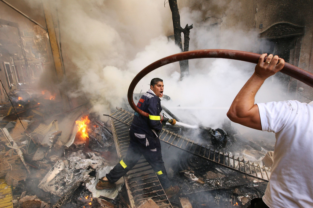 . Firefighters extinguish fire at the scene of an explosion in Ashrafieh, central Beirut October 19, 2012. A huge car bomb exploded in a street in central Beirut during rush hour on Friday, killing at least eight people and wounding about 80, witnesses and officials said.  REUTERS/Hasan Shaaban