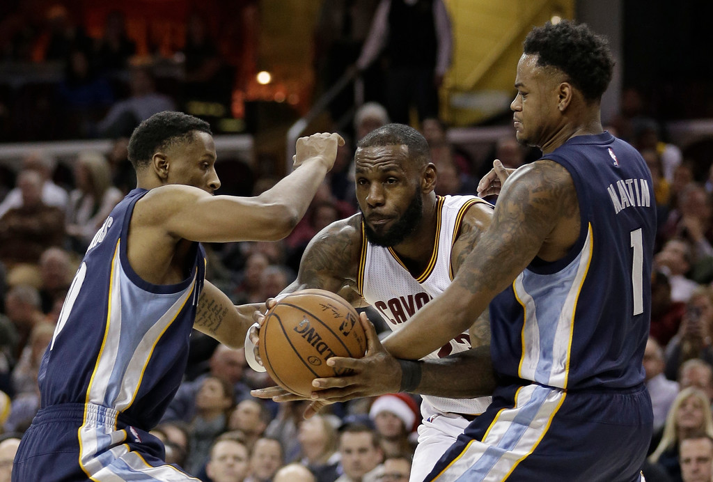 . Cleveland Cavaliers\' LeBron James, center, drives between Memphis Grizzlies\' Troy Williams, left, and Jarell Martin in the second half of an NBA basketball game, Tuesday, Dec. 13, 2016, in Cleveland. The Cavaliers won 103-86. (AP Photo/Tony Dejak)