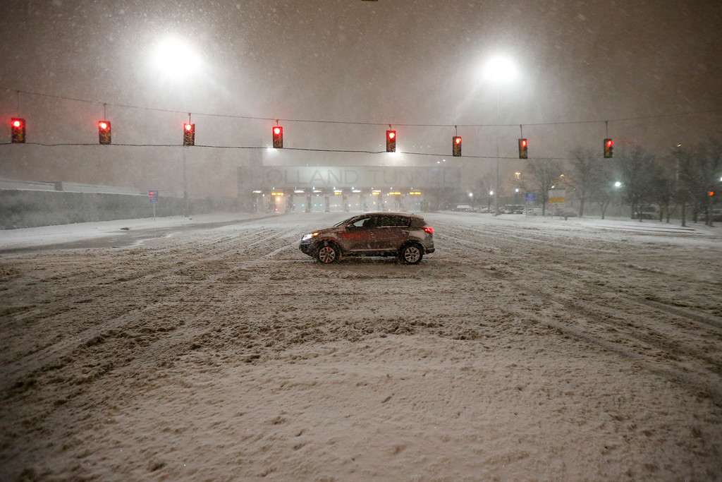 . A vehicle crosses a snow-covered road near the Holland Tunnel during a snowstorm, Saturday, Jan. 23, 2016, in Jersey City, N.J. Towns across the state are hunkering down during a major snowstorm that hit overnight. (AP Photo/Julio Cortez)