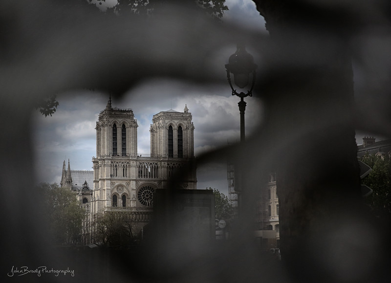 Reflection of Notre Dame Cathedral in a wrought iron and glass window in a nearby church door  - JohnBrody.com / John Brody Photography
