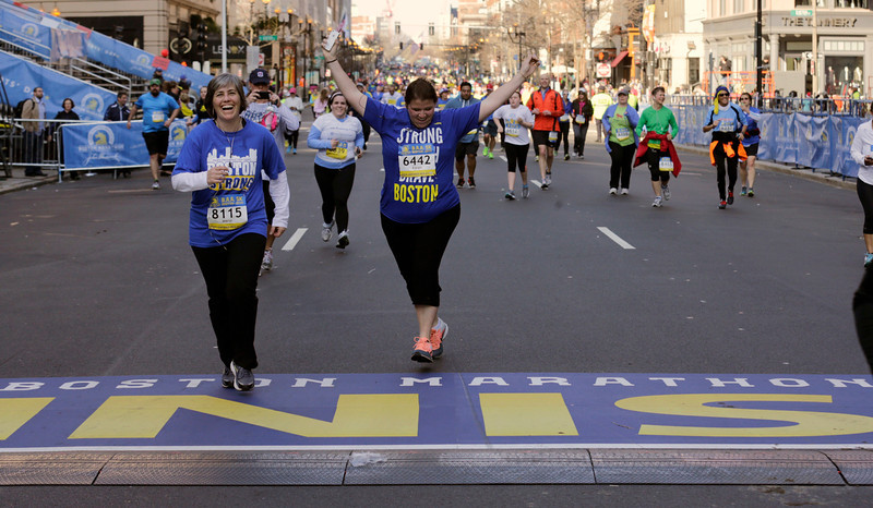 . Karen Faich, of Hanson, Mass., raises her arm as she crosses the midpoint of the 5k race, the finish line of the Boston Marathon, Saturday, April 19, 2014 in Boston. The 118th Boston Marathon is scheduled to run on Patriots Day, Monday, April 21. (AP Photo/Charles Krupa)