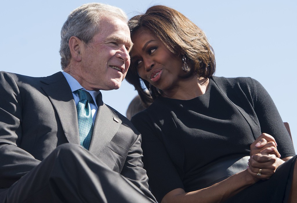 ". Former US President George W. Bush speaks with First Lady Michelle Obama  during an event marking the 50th Anniversary of the Selma to Montgomery civil rights marches at the Edmund Pettus Bridge in Selma, Alabama, March 7, 2015. US President Barack Obama rallied a new generation of Americans to the spirit of the civil rights struggle, warning their march for freedom ""is not yet finished.\"" In a forceful speech in Selma, Alabama on the 50th anniversary of the brutal repression of a peaceful protest, America\'s first black president denounced new attempts to restrict voting rights. AFP PHOTO/ SAUL  LOEB/AFP/Getty Images"