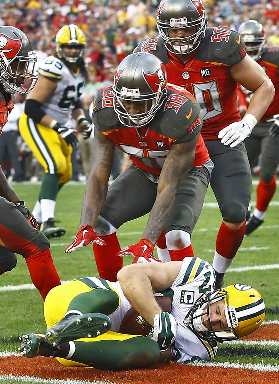 . Green Bay Packers wide receiver Jordy Nelson, bottom, falls into the end zone in front of Tampa Bay Buccaneers free safety Dashon Goldson (38) and middle linebacker Dane Fletcher (50) after catching a 1-yard touchdown pass during the fourth quarter of an NFL football game Sunday, Dec. 21, 2014, in Tampa, Fla. (AP Photo/Brian Blanco)