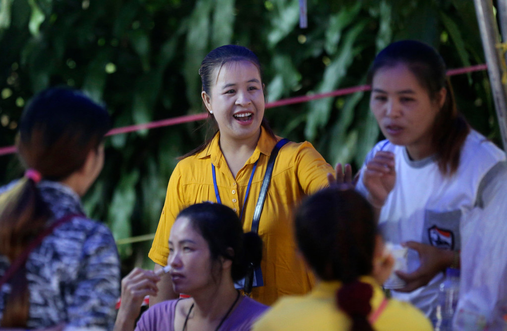 . Family members talk together while waiting near a cave where 12 boys and their soccer coach are trapped, in Mae Sai, Chiang Rai province, in northern Thailand, Thursday, July 5, 2018. A Thai official overseeing the rescue operation of the soccer team trapped in the flooded cave said they may not all be extracted at the same time depending on their health. (AP Photo/Sakchai Lalit)