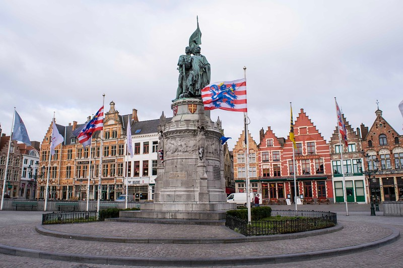 a statue of two men in a round plaza, with a flag