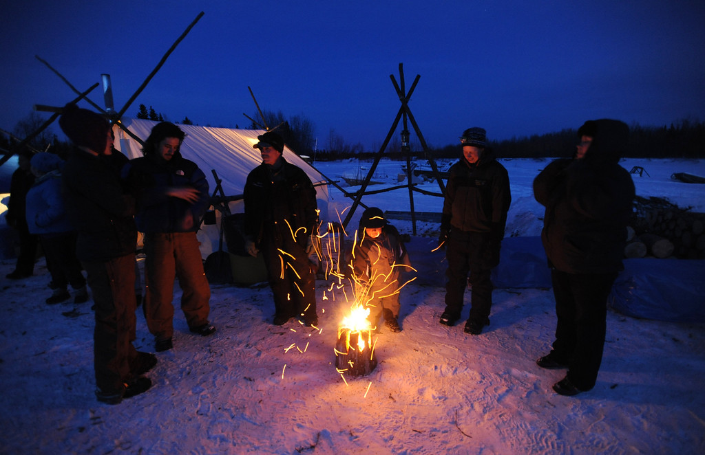 . Four-year-old Kayden Alexie pokes a fire with a stick as people gather in the village of Nikolai, Alaska, to watch and help with dog teams pulling into the checkpoint during the Iditarod Trail Sled Dog Race, Tuesday, March 5, 2013. (AP Photo/Anchorage Daily News, Bill Roth)