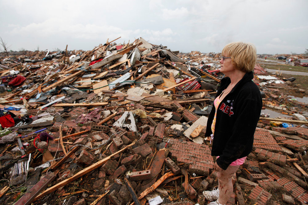 . Resident Kim Schwab looks over her destroyed home in south Oklahoma City, Monday, May 20, 2013. A monstrous tornado roared through the Oklahoma City suburbs, flattening entire neighborhoods with winds up to 200 mph, setting buildings on fire and landing a direct blow on an elementary school. (AP Photo/The Oklahoman, Paul Hellstern)