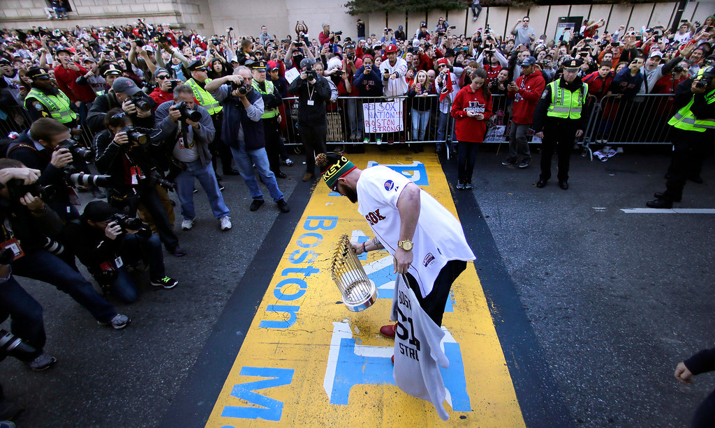 . Boston Red Sox\'s Jonny Gomes puts the 2013 World Series trophy and a team jersey on the finish line of the Boston Marathon, in honor of those affected by the bombings, as they stopped the parade in celebration of the baseball team\'s World Series win, Saturday, Nov. 2, 2013, in Boston. (AP Photo/Charles Krupa)