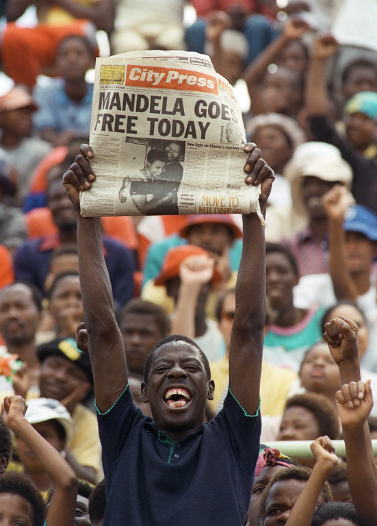 . A jubilant Sowetan holds up  February 11,1990 in Soweto, a newspaper announcing the release of anti-apartheid leader and African National Congress (ANC) member Nelson Mandela, at a mass ANC rally. South African President de Klerk lifted  February 2, 1980 the 30-year-old ban on the ANC and the South African Communikst Party, and 11 February, Nelson Mandela walked out of Victor Vester prison, near Cape Town, after 26 year since he  was sentenced to life imprisonment.        (TREVOR SAMSON/AFP/Getty Images)