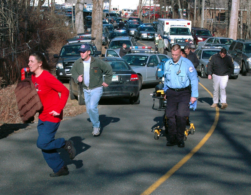 . In this photo provided by the Newtown Bee, paramedics and others rush toward Sandy Hook Elementary School in Newtown, Conn., where authorities say a gunman opened fire, killing 26 people, including 20 children, Friday, Dec. 14, 2012. (AP Photo/Newtown Bee, Shannon Hicks)