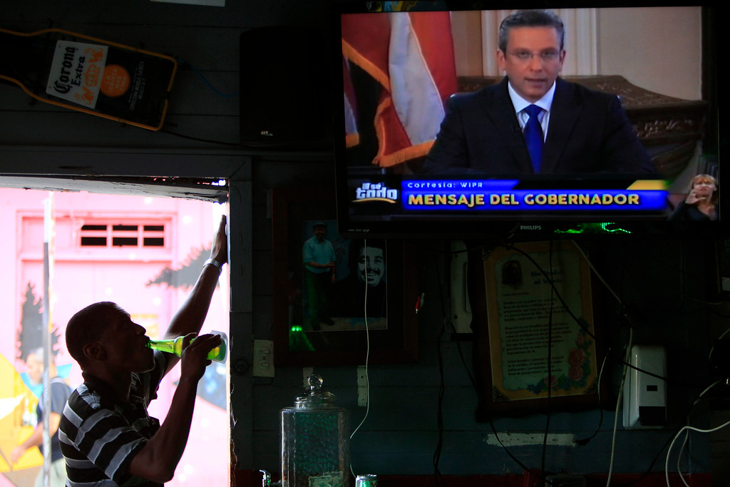. A man drinks a beer in a local bar as he watches Puerto Rico�s governor Alejandro Garcia Padilla on television delivering an address on the state of the island\'s finances, in San Juan, Puerto Rico, Monday, June 29, 2015. The governor said that he will form a financial team to negotiate with bondholders on delaying debt payments and then restructuring $72 billion in public debt that he says the island can\'t repay. (AP Photo/Ricardo Arduengo)