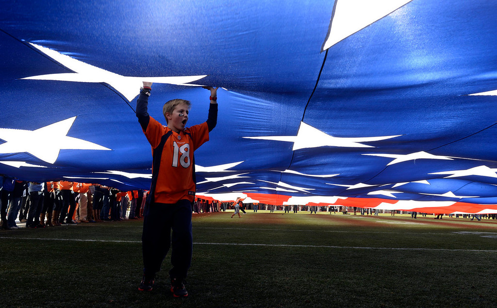 . A young Broncos fan assists in holding up the giant U.S. flag prior to the game.  The Denver Broncos vs. The New England Patriots in an AFC Championship game  at Sports Authority Field at Mile High in Denver on January 19, 2014. (Photo by Helen Richardson/The Denver Post)