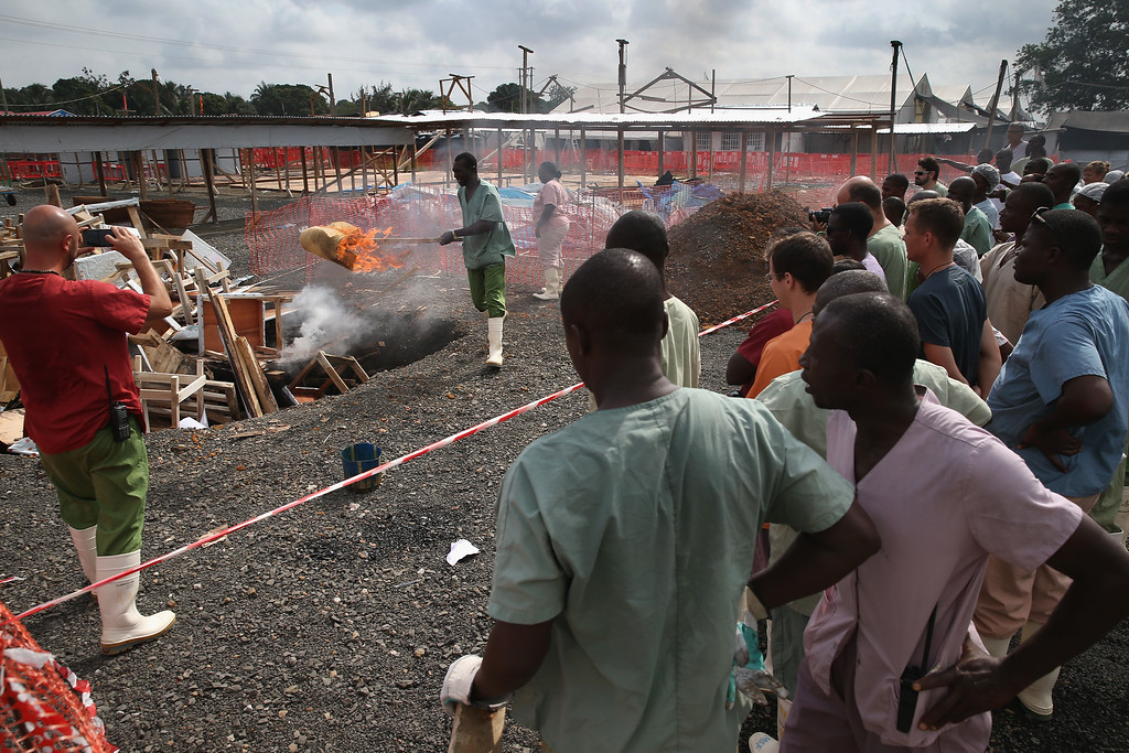 . Health workers from Doctors Without Borders (MSF), watch as Ebola survivor Jessy Amos, 45, lights fire to furnature from the Ebola Treatment Unit (ETU), on January 26, 2015 in Paynesville, Liberia.   (Photo by John Moore/Getty Images)