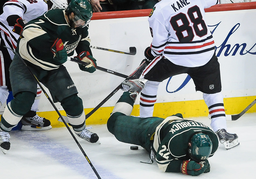 . Minnesota right wing Cal Clutterbuck falls the to the ice after being slapped in the face with a stick in the third period against the Blackhawks.  (Pioneer Press: Ben Garvin)