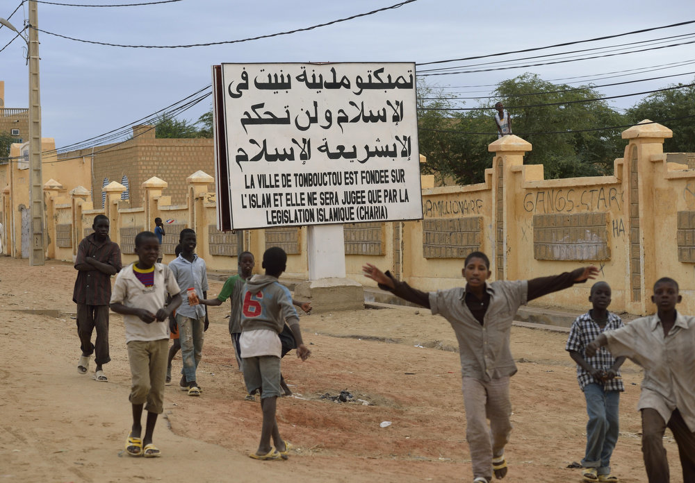 "Description of . Children wave after Malian and French soldiers entered the historic city of Timbuktu, occupied for 10 months by Islamists who imposed a harsh form of sharia, on January 28, 2013. Hundreds of people scrambled Monday to give French-led troops a hero\'s welcome as they entered the city. Sings reads ""The city of Timbuktu is founded on Islam and will be judged only by the Islamic law.\""    ERIC FEFERBERG/AFP/Getty Images"