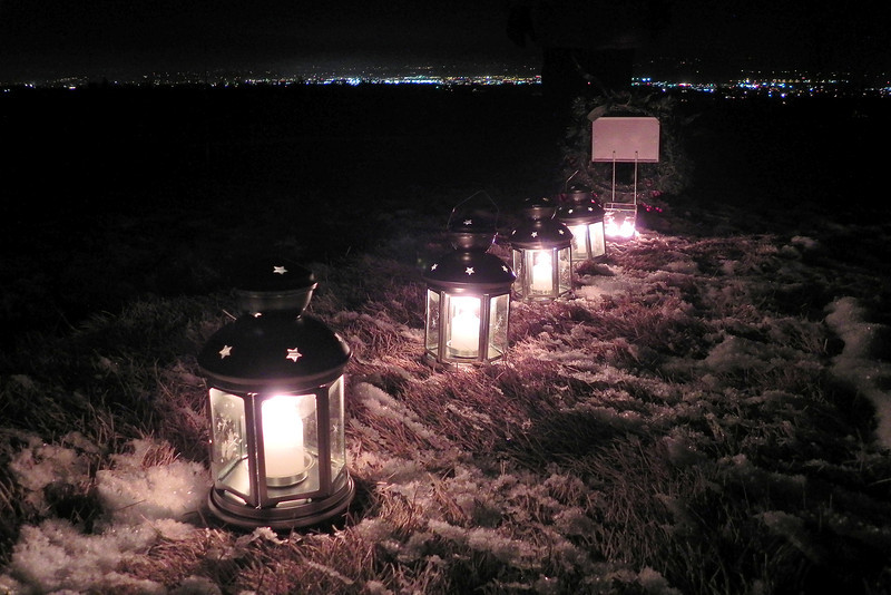 """2011/12/23 – It is Christmas eve eve, or what Lisa's dad called, """"Christmas Adam because Adam came before Eve."""" We picked up these lanterns and candles at IKEA and placed them on Raija's grave above Logan, seen in the distance. We stood there in the freezing cold and sang Silent Night. When we finished and stood in the silence to take in the lanterns we realized it wasn't silent. The coyotes had joined in song with us during Silent Night and obviously knew one more verse than we knew. It was spooky how close they sounded."""