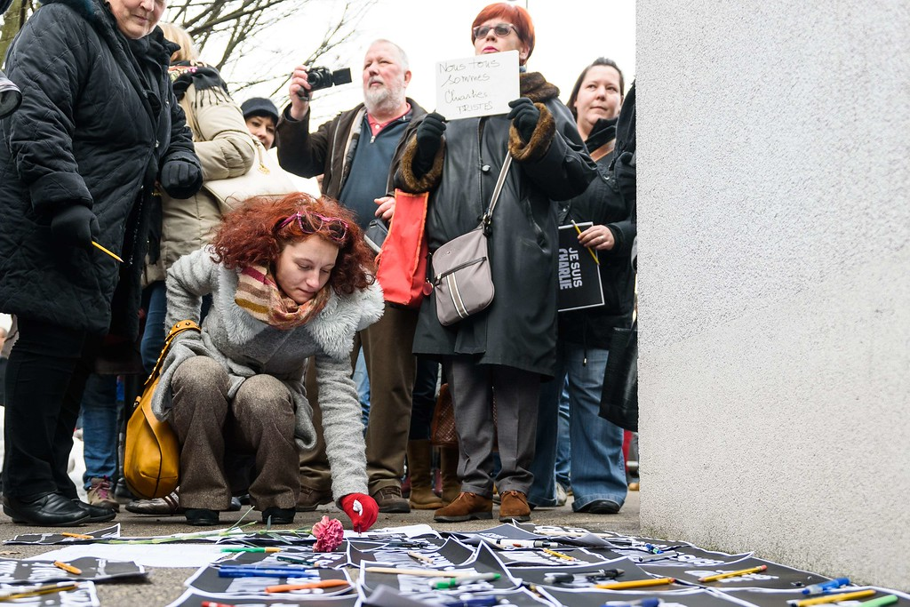 ". A woman lays a pen among placards reading in French ""I am Charlie\"" in front of the French embassy during a gathering in tribute of victims of the attack on French satirical weekly Charlie Hebdo, on January 8, 2015 in Ljubljana, a day after two gunmen killed 12 people in an Islamist attack at Charlie Hebdo\'s editorial office in Paris. The massacre, the country\'s bloodiest attack in half a century, triggered poignant and spontaneous demonstrations of solidarity around the world. Charlie Hebdo is famed for its irreverent views of religion and its decision to publish controversial cartoons of the prophet Mohammed. AFP PHOTO / JURE  Makovec/AFP/Getty Images"