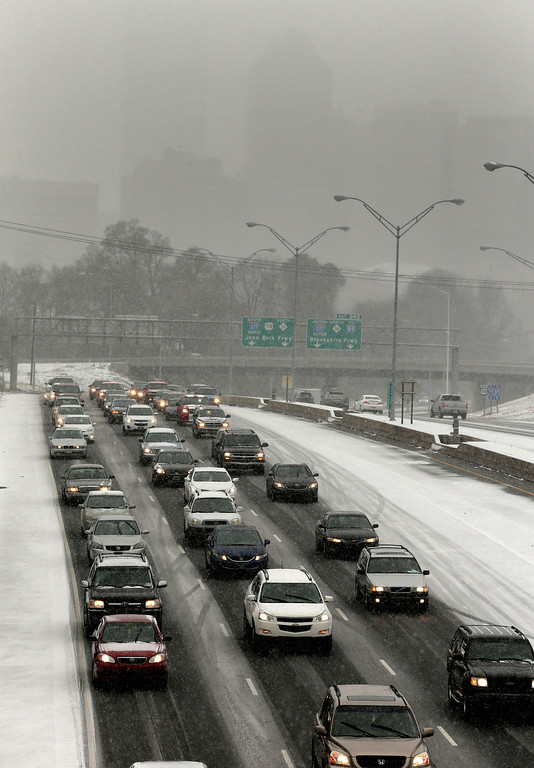 . Drivers pack the roads as they leave downtown Charlotte, N.C., Wednesday, Feb. 12, 2014, as a winter storm moves into the area. (AP Photo/Chuck Burton)