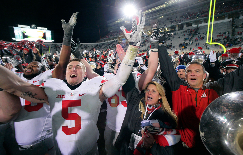 . Ohio State\'s Jeff Heuerman (5), coach Urban Meyer, right, and Meyer\'s wife, Shelley, celebrate following the team\'s 49-37 win over Michigan State in an NCAA college football game, early Sunday, Nov. 9, 2014, in East Lansing, Mich. (AP Photo/Al Goldis)