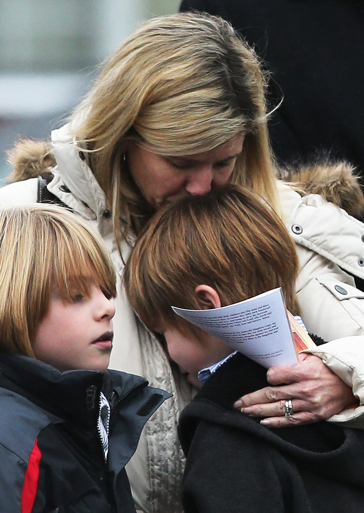 Description of . A woman comforts a boy as mourners depart Honan Funeral Home after the funeral for six-year-old Jack Pinto on December 17, 2012 in Newtown Connecticut. Pinto was one of the 20 students killed in the Sandy Hook Elementary School mass shooting.  (Photo by Mario Tama/Getty Images)