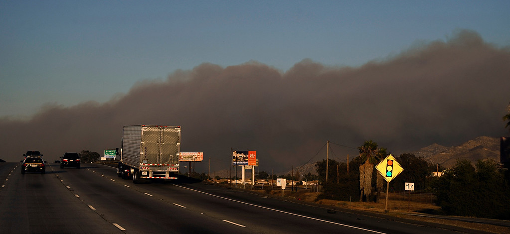 . Thick black smoke blows over the Interstate 10 from the Silver Fire near Banning, California August 7, 2013.  Hundreds of residents of three small communities in the high desert east of Los Angeles were evacuated on Wednesday as an out-of-control wildfire headed toward them.    Photo by Gene Blevins/LA Daily News