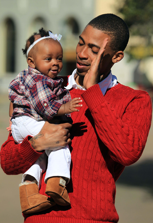 """. Darrell \""""D-Real\"""" Armstead high-fives his daughter Dr\'eal Armstead, 5 months, at Frank Ogawa Plaza in Oakland, Calif., on Friday, Feb. 22, 2013.  (Jane Tyska/Staff)"""