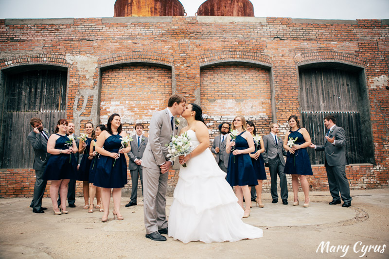 Matt & Larissa kissing in front of their bridesmaids and groomsmen at the McKinney Cotton Mill | Photo by Mary Cyrus Photography - Weddings & Portraits in Dallas & Beyond