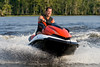 Man riding wave runner in a river, enjoying a nice summer day.