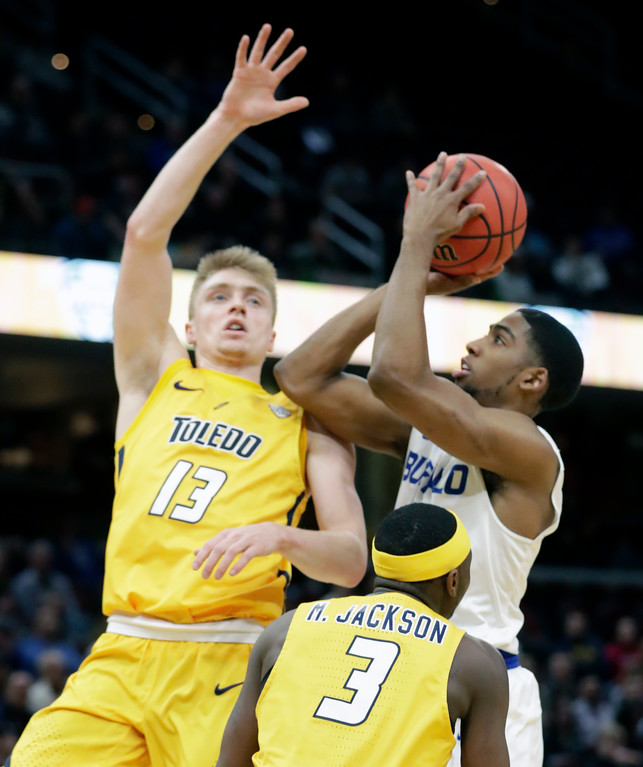 . Buffalo\'s CJ Massinburg (5) shoots against Toledo\'s Jaelan Sanford (13) and Marreon Jackson (3) during the first half of an NCAA college basketball championship game of the Mid-American Conference tournament, Saturday, March 10, 2018, in Cleveland. (AP Photo/Tony Dejak)