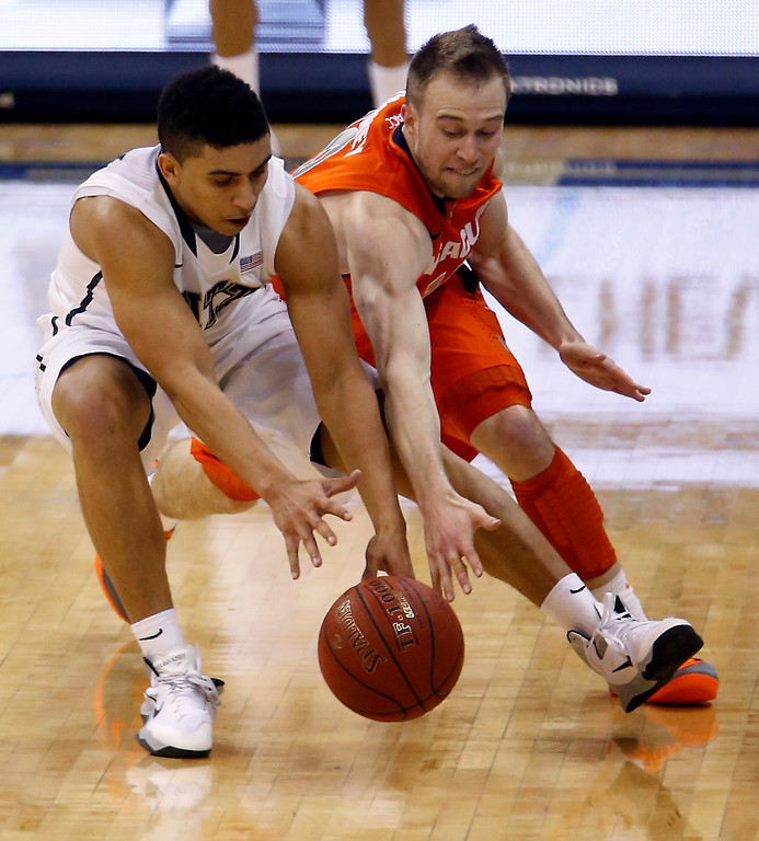 . Pittsburgh\'s James Robinson, left, and Syracuse\'s Trevor Cooney go for a loose ball during the second half of an NCAA college basketball game on Wednesday, Feb. 12, 2014, in Pittsburgh. (AP Photo/Keith Srakocic)