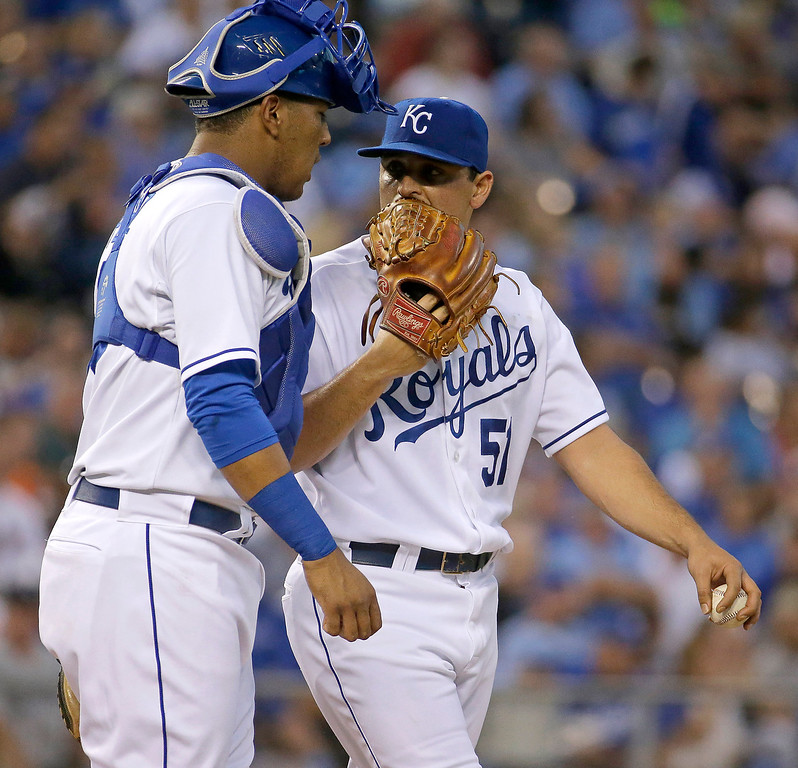 . Kansas City Royals starting pitcher Jason Vargas talks with catcher Salvador Perez after giving up two runs during the first inning of a baseball game against the Detroit Tigers on Friday, Sept. 19, 2014, in Kansas City, Mo. (AP Photo/Charlie Riedel)