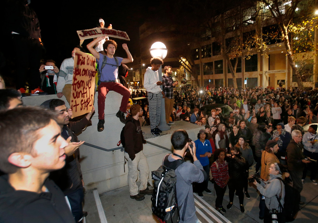 . Marchers stop in front of City Hall in Berkeley, Calif., Sunday evening, Dec. 7, 2014, as they protested the killings of two unarmed black men by police in Ferguson, Mo., and New York.   (Karl Mondon/Bay Area News Group)