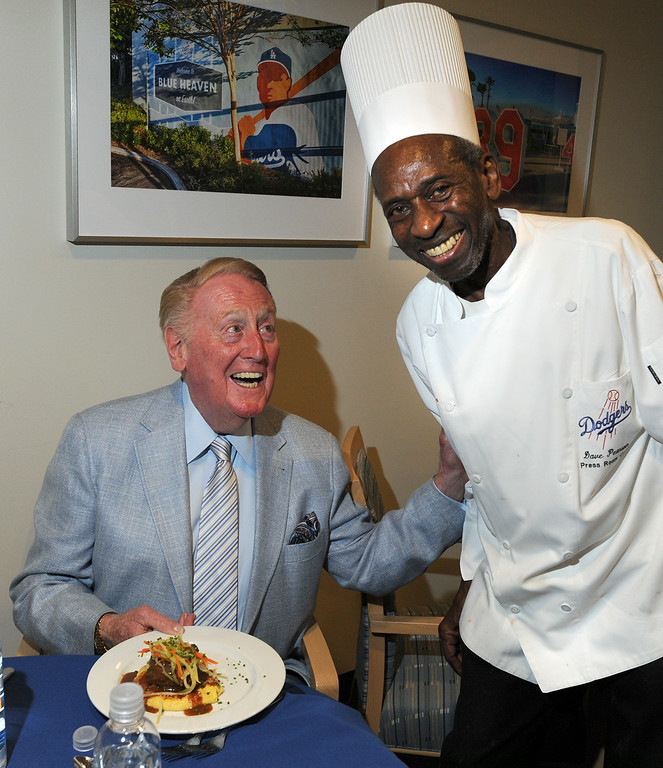 . Vin Scully gets served a meal by Dave Pearson who has been cooking up meals in the Dodger Press box for many years.  Los Angeles, CA. 8/19/2014(Photo by John McCoy Daily News)