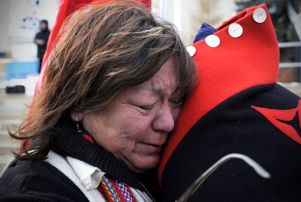 Description of . Taz Bouchier, an elder with the Idle No More movement, hugs a supporter after her speech at a rally in solidarity with the Washington D.C. protest against the Keystone XL pipeline and for environmental action in Edmonton February 17, 2013. The TransCanada Corp pipeline would link the oil sands of northern Alberta, the world's third largest crude resource, to refineries and ports in Texas. Environmentalists say approval of the pipeline will encourage more development in the oil sands, where extraction is carbon intensive, leading to greater greenhouse gas emissions.     REUTERS/Dan Riedlhuber