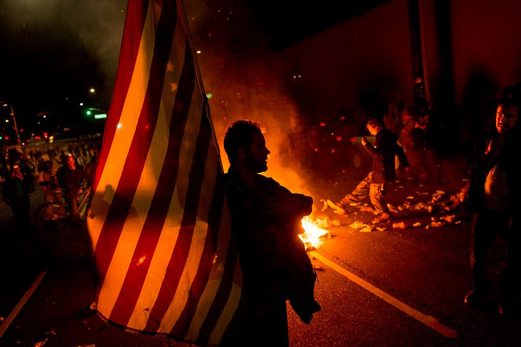 . James Cartmill holds an American flag while protesting in Oakland, Calif., on Monday, Nov. 24, 2014, after the announcement that a grand jury decided not to indict Ferguson police officer Darren Wilson in the fatal shooting of Michael Brown, an unarmed 18-year-old. Several thousand protesters marched through Oakland with some shutting down freeways, looting, burning garbage and smashing windows. (AP Photo/Noah Berger)