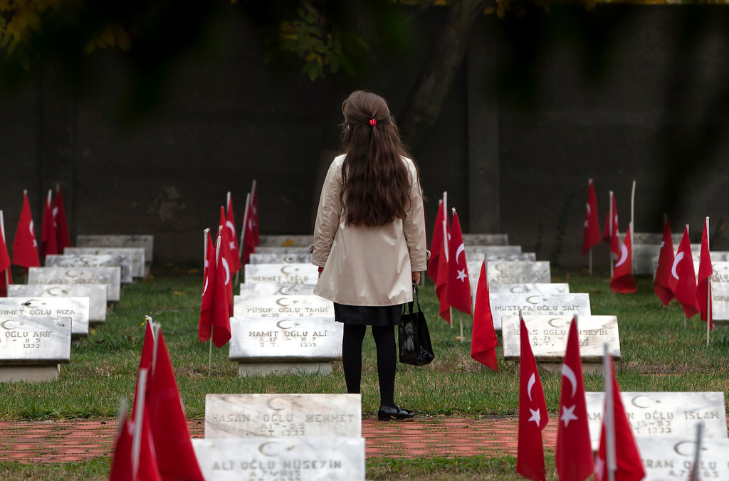 . A child of the Turkish community stands  between graves at the Turkish Heroes cemetery in Bucharest, Romania, Tuesday, Oct. 15, 2013 after Eid al Adha prayers.  (AP Photo/Vadim Ghirda)