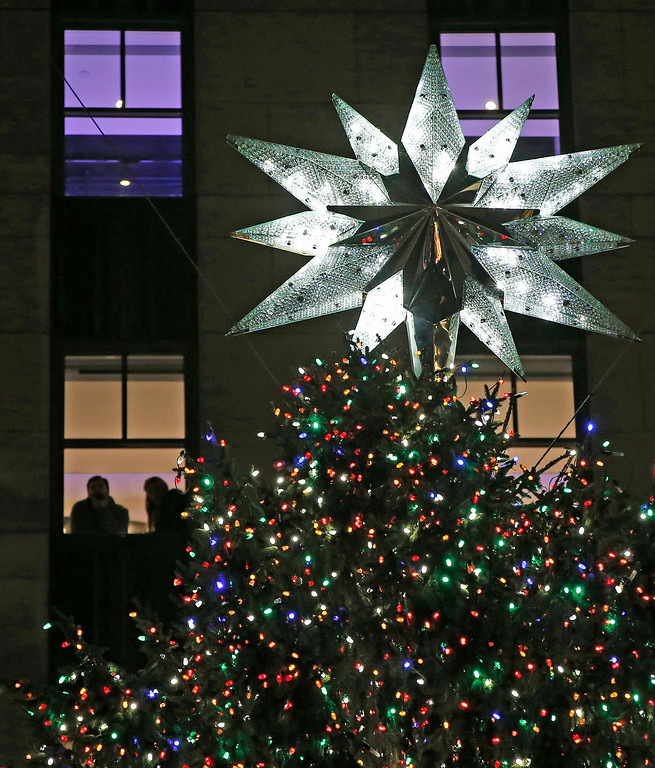 . People look out a fifth-story window at the Swarovski star atop the Rockefeller Center Christmas tree after it was lit during a ceremony, Wednesday, Dec. 4, 2013, in New York. Some 45,000 energy efficient LED lights adorn the 76-foot tree. (AP Photo/Kathy Willens)