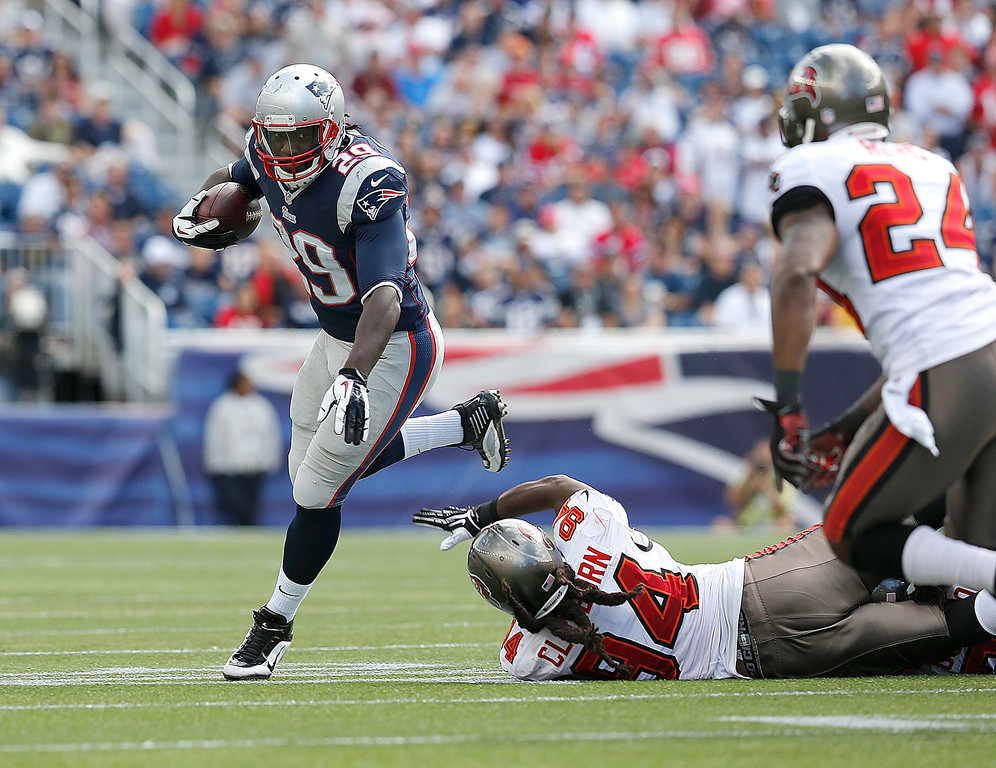. LeGarrette Blount #29 of the New England Patriots leaps over Adrian Clayborn #94 of the Tampa Bay Buccaneers in the second half in a game at Gillette Stadium on September 22, 2013 in Foxboro, Massachusetts. (Photo by Jim Rogash/Getty Images)