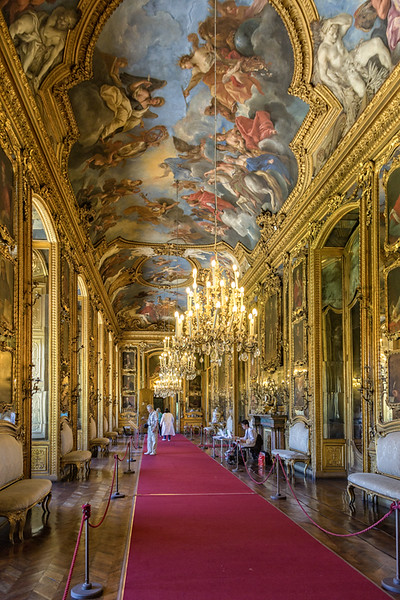 extra long hallway with red carpet and ceiling artwork