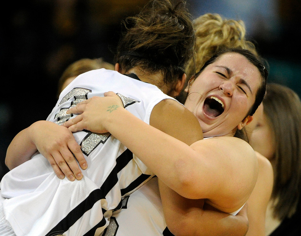 . DENVER, CO. - MARCH 9TH: Megan Valdez, right, Pueblo South High School, celebrates with teammate, Shannon Patterson with a bear hug after her team defeated Mesa Ridge High School, 54-33,  in the 4A �Great Eight� game at the Denver Coliseum, Saturday morning, March 9th, 2013. Pueblo South won 54-33 to advance to the Final Four at the CU Events Center, March 14th, 2013. (Photo By Andy Cross The Denver Post)