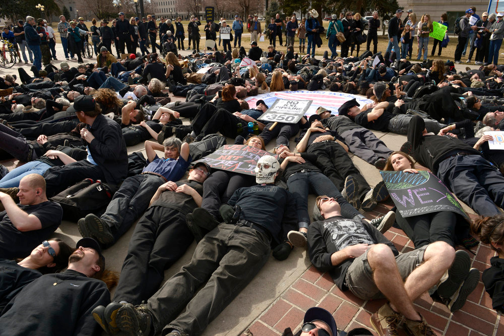 . All of the protestors wore black and lay down in Civic Center park to act as a human oil spill during the rally.  A few hundred people from a coalition of students, faith-based organizations, indigenous, political, and environmental groups marched from the Denver Auraria campus and ended in a rally at Civic Center Park on February 17th, 2013.  The march, called the #ForwardOnClimate Solidarity March and rally, organized by the Sierra Club, 350.org and GoFossilFree.org,  coincided with tens of thousands of protestors, who converged on Washington, DC for the largest climate rally in history. Denver was one of 18 cities hosting major actions to show solidarity with the DC event.    (Photo By Helen H. Richardson/ The Denver Post)