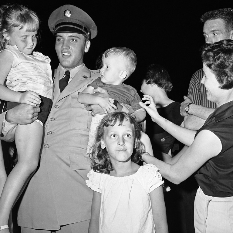 . Elvis Presley, 23, home on furlough after 8 weeks basic training, with a couple of the fans who besieged the gate to his $100,000 mansion in Memphis, Tennessee on June 2, 1958.  He�s holding Donna Harrison, 5, and Ronnie Brown, 2, both of Memphis. (AP Photo)