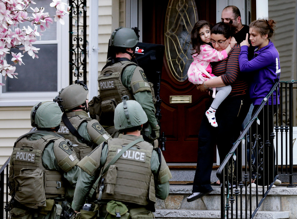 . In this Friday, April 19, 2013 file photo, a woman carries a girl from a home as a SWAT team searching for a suspect in the Boston Marathon bombings enters the building in Watertown, Mass. (AP Photo/Charles Krupa)