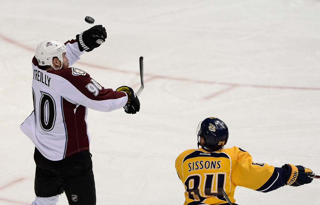 . Colorado Avalanche center Ryan O\'Reilly (90) knocks the  puck down in front of Nashville Predators forward Colton Sissons (84) in the second period of an NHL hockey game on Tuesday, March 25, 2014, in Nashville, Tenn. (AP Photo/Mark Zaleski)