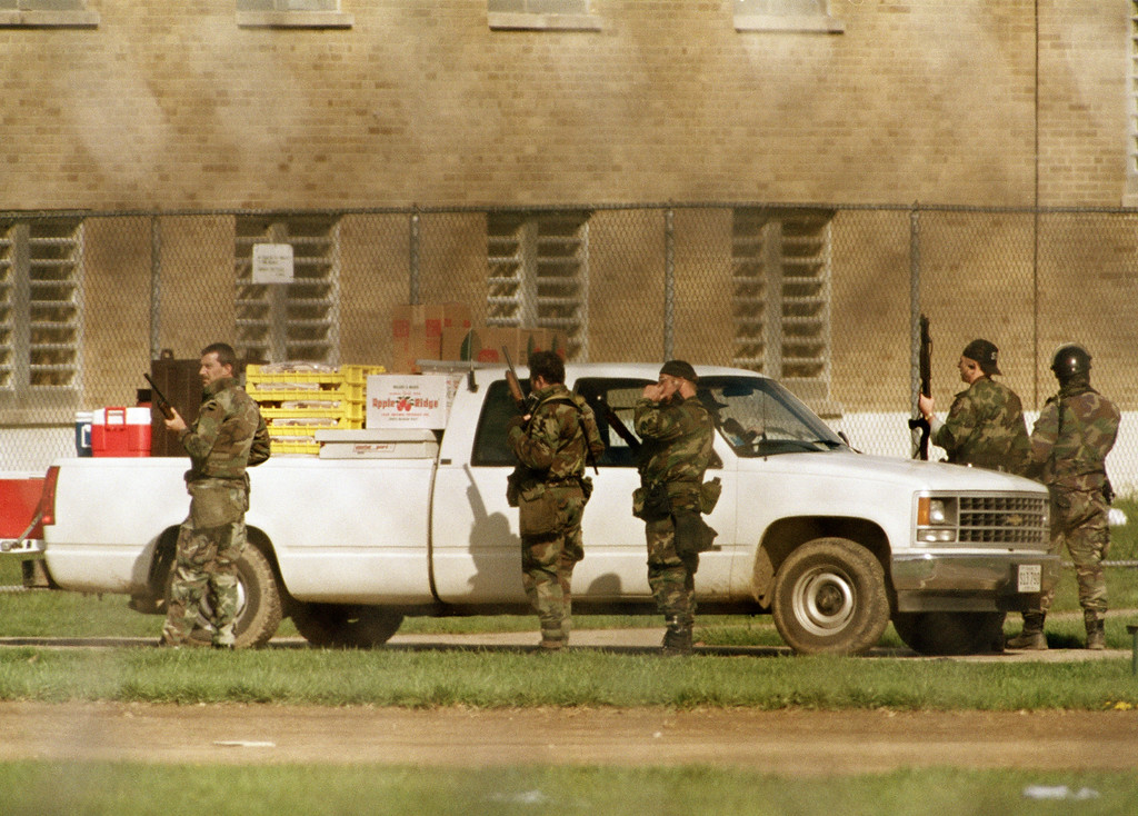 . Armed guards deliver food in a pickup truck inside the recreation yard at Southern Ohio Correction Facility, April 17, 1993. The food was retrieved by inmates holding five guards hostage on the sixth day of a siege. (AP Photo/Mark Duncan)