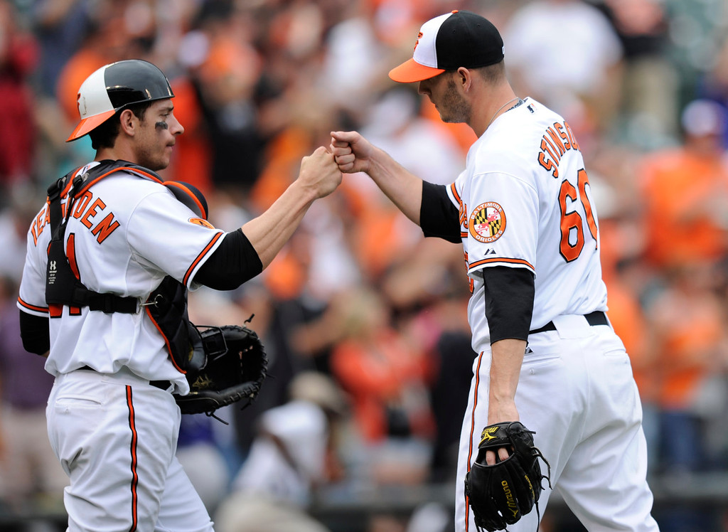 . Baltimore Orioles relief pitcher Josh Stinson (60) celebrates a 7-2 win over the Colorado Rockies with catcher Taylor Teagarden, left, after a baseball game on Sunday, Aug. 18, 2013, in Baltimore. (AP Photo/Nick Wass)