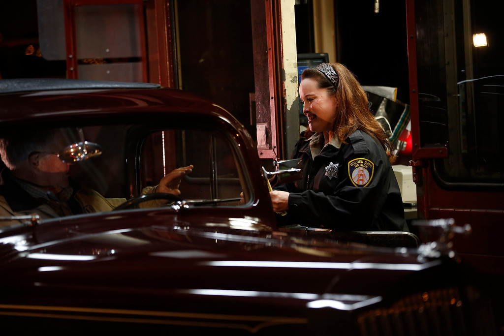 . Toll collector Marilyn Alvardo (R) receives the last toll from Jim Eddie, who is driving a vintage 1937 Packard, at her tollbooth at the Golden Gate Bridge toll plaza in San Francisco, California March 27, 2013. The Golden Gate Bridge will convert from manned tollbooths to a full electronic tolling system starting March 27. With the automated system in place, motorists will have the option of using the existing FasTrak electronic toll collection system or the newly implemented pay-by-plate option, according to Golden Gate Bridge management. REUTERS/Stephen Lam