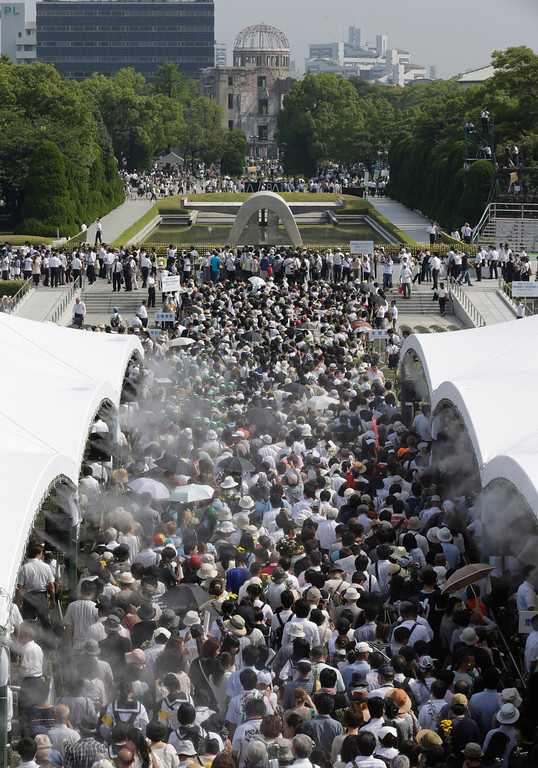 . People wait in line to offer prayers in front of the cenotaph, center, dedicated to the victims of the atomic bombing at the Hiroshima Peace Memorial Park after the ceremony to mark the 68th anniversary of the bombing, in Hiroshima, western Japan, Tuesday, Aug. 6, 2013. (AP Photo/Shizuo Kambayashi)
