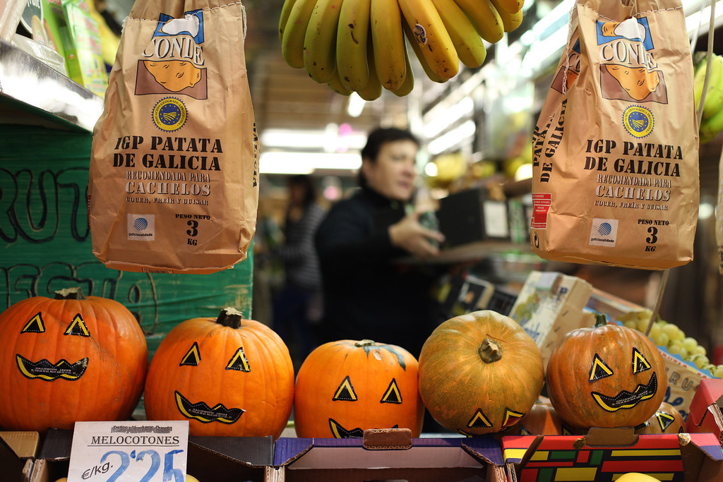 . A storekeeper attends a client next to Halloween decorated pumpkins at Madrid\'s La Cebada food market, Thursday, Oct. 31, 2013. Pumpkins are traditionally bought and decorative faces carved out of them before masked costume parties at night to mark Halloween which occurs annually around the world on October 31. (AP Photo/Francisco Seco)
